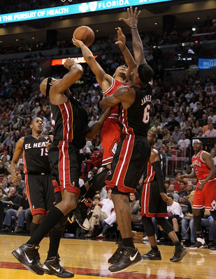 MIAMI, FL - MARCH 06:  Derrick Rose #1 of  the Chicago Bulls shoots over LeBron James #6 and Eric Dampier #25 of the Miami Heat during a game at American Airlines Arena on March 6, 2011 in Miami, Florida. NOTE TO USER: User expressly acknowledges and agre