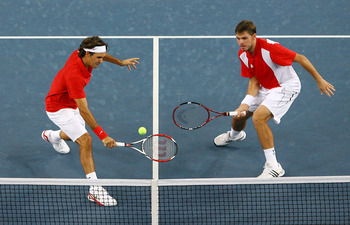 BEIJING - AUGUST 16:  Roger Federer (left) and Stanislas Wawrinka of Switzerland take on Thomas Johansson and Simon Aspelin of Sweden during the men's doubles gold medal tennis match at the Olympic Green Tennis Center on Day 8 of the Beijing 2008 Olympic