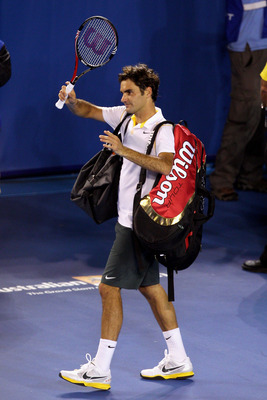 MELBOURNE, AUSTRALIA - JANUARY 27:  Roger Federer of Switzerland walks off court after losing his semifinal match against Novak Djokovic of Serbia during day eleven of the 2011 Australian Open at Melbourne Park on January 27, 2011 in Melbourne, Australia.