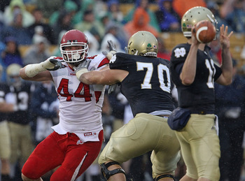 SOUTH BEND, IN - NOVEMBER 13: Dave Kruger #44 of the Utah Utes rushes against Zack Martin #70 of the Notre Dame Fighting Irish as Tommy Rees #13 passes the ball at Notre Dame Stadium on November 13, 2010 in South Bend, Indiana. Notre Dame defeated Utah 28