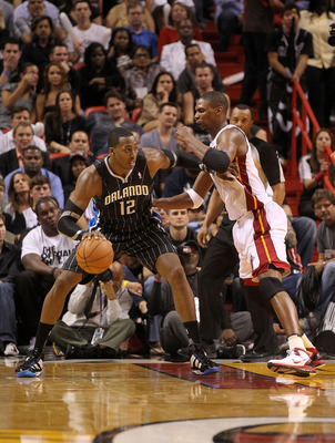 MIAMI, FL - MARCH 03:  Dwight Howard #12 of the Orlando Magic drives against Chris Bosh #1 of the Miami Heat during a game at American Airlines Arena on March 3, 2011 in Miami, Florida. NOTE TO USER: User expressly acknowledges and agrees that, by downloa