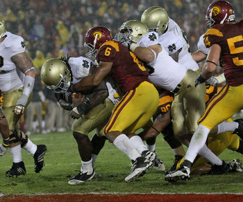 LOS ANGELES, CA - NOVEMBER 27:  Running back Robert Hughes #33 of the Notre Dame Fighting Irish carries on a five yard run to score the eventual winning touchdown in the fourth quarter through the tackle of linebacker Malcolm Smith #6 of the USC Trojans a
