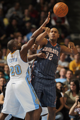 DENVER, CO - MARCH 02:  Boris Diaw #32 of the Charlotte Bobcats dishes the ball off against the defense of Raymond Felton #20 of the Denver Nuggets at the Pepsi Center on March 2, 2011 in Denver, Colorado. NOTE TO USER: User expressly acknowledges and agr