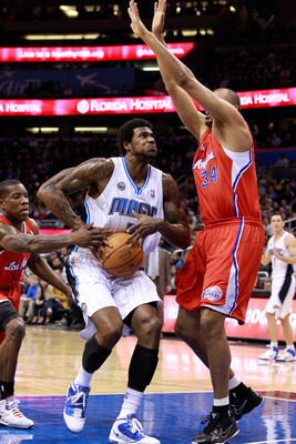 ORLANDO, FL - FEBRUARY 08:  Earl Clark #3 of the Orlando Magic attempts a shot against Brian Cook #34 of the Los Angeles Clippers during the game at Amway Arena on February 8, 2011 in Orlando, Florida.  NOTE TO USER: User expressly acknowledges and agrees