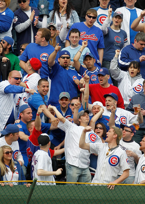 CHICAGO - APRIL 12: Chicago Cub fans in the right field bleachers encourage another fan to throw a home run ball hit by Ryan Braun of the Milwaukee Brewers back onto the field on Opening Day at Wrigley Field on April 12, 2010 in Chicago, Illinois. The Cub
