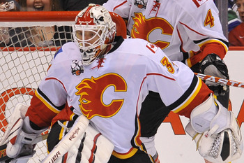 VANCOUVER, CANADA - MARCH 14: Curtis Glencross #20 of the Calgary Flames clears the puck away from the front of the net after goalie Miikka Kiprusoff #34 made the initial save during the first period of NHL action against the Vancouver Canucks on March 14