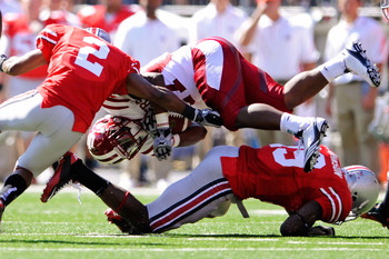 COLUMBUS, OH - OCTOBER 9:  Antonio Banks #27 of the Indiana Hoosiers is upended by Orhian Johnson #19 and Christian Bryant #2 of the Ohio State Buckeyes at Ohio Stadium on October 9, 2010 in Columbus, Ohio.  (Photo by Jamie Sabau/Getty Images)