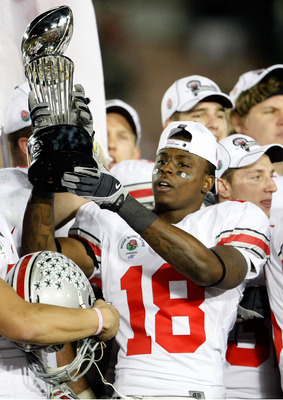 PASADENA, CA - JANUARY 01:  Cornerback Travis Howard #18 of the Ohio State Buckeyes celebrates with the Rose Bowl championship trophy after the Buckeyes 26-17 win over the Oregon Ducks in the 96th Rose Bowl game on January 1, 2010 in Pasadena, California.