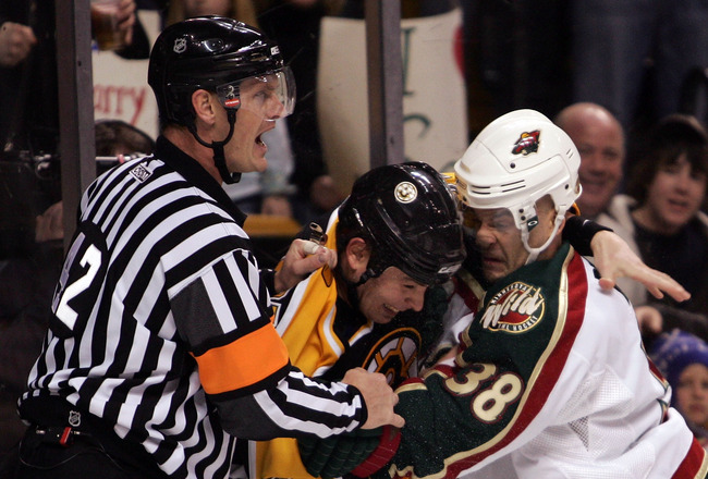 BOSTON - MARCH 8:  Referee Dan O'Rourke #42 tries to break up a fight between Pavol Demitra #38 of the Minnesota Wild and Marc Savard #91 of the Boston Bruins on March 8, 2007 at the TD Banknorth Garden in Boston, Massachusetts. (Photo by Elsa/Getty Image