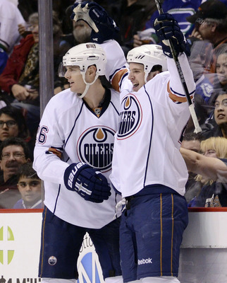 VANCOUVER, CANADA - DECEMBER 26: Ryan O'Marra #42 of the Edmonton Oilers celebrates with Kurtis Foster #26 after scoring his first goal of the season against the Vancouver Canucks during the second period in NHL action on December 26, 2010 at Rogers Arena