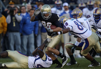 SOUTH BEND, IN - OCTOBER 30: Bennett Jackson #86 of the Notre Dame Fighting Irish is tackled by Donnell Hawkins #43 and Bryan Burnham #88 of the Tulsa Golden Hurricane at Notre Dame Stadium on October 30, 2010 in South Bend, Indiana. Tulsa defeated Notre