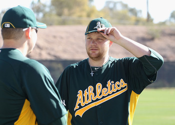 PHOENIX, AZ - FEBRUARY 16:  (L-R) Pitchers Trevor Cahill #53 and Brett Anderson #49 of the Oakland Athletics warm up during a MLB spring training practice at Phoenix Municipal Stadium on February 16, 2011 in Phoenix, Arizona.  (Photo by Christian Petersen