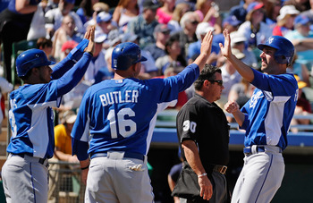 MESA, AZ - MARCH 09:  Mike Aviles #13, Billy Butler #16 and Jeff Francoeur #21 of the Kansas City Royals celebrate after they all scored on a triple by teammate Melky Cabrera #53 in the first inning against pitcher Matt Garza #17 of the Chicago Cubs durin