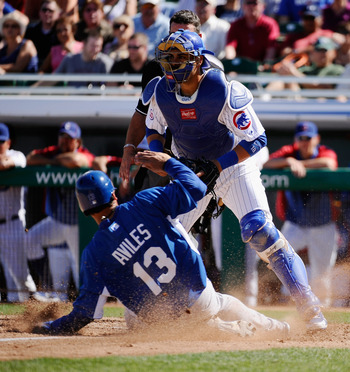 MESA, AZ - MARCH 09: Catcher Geovany Soto #18 of the Chicago Cubs looks for the throw to home plate as Mike Aviles #13 of the Kansas City Royals scores a run in the fourth inning of the spring training baseball game at HoHoKam Stadium on March 9, 2011 in