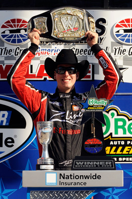 FORT WORTH, TX - NOVEMBER 07:  Kyle Busch, driver of the #18 Z-Line Designs/WWE Smackdown Toyota,  hoist a replica of the WWE world championship belt on victory lane after winning the NASCAR Nationwide Series O'Reilly Challenge at Texas Motor Speedway on