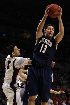 PORTLAND, OR - MARCH 19:  Nikola Cvetinovic #13 of the Akron Zips grabs a rebound against Austin Daye #5 of the Gonzaga Bulldogs in the second half during the first round of the NCAA Division I Men's Basketball Tournament at the Rose Garden on March 19, 2