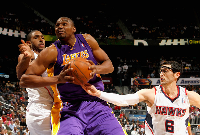 ATLANTA, GA - MARCH 08:  Andrew Bynum #17 of the Los Angeles Lakers drives between Al Horford #15 and Kirk Hinrich #6 of the Atlanta Hawks at Philips Arena on March 8, 2011 in Atlanta, Georgia.  NOTE TO USER: User expressly acknowledges and agrees that, b