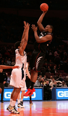 NEW YORK, NY - MARCH 10: Yancy Gates #34 of the Cincinnati Bearcats shoots over Tyrone Nash #1 of the Notre Dame Fighting Irish during the quarterfinals of the 2011 Big East Men's Basketball Tournament presented by American Eagle Outfitters  at Madison Sq