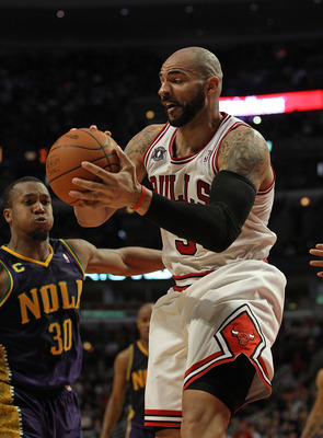 CHICAGO, IL - MARCH 07: Carlos Boozer #5 of the Chicago Bulls grabs a rebound next to David West #30 of the New Orleans Hornets at the United Center on March 7, 2011 in Chicago, Illinois. The Bulls defeated the Hornets 85-77. NOTE TO USER: User expressly