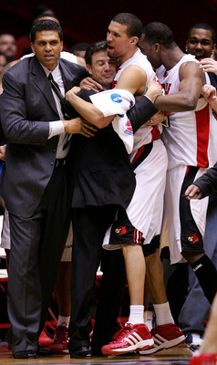 ALBUQUERQUE, NM - MARCH 26:  Head coach Rick Pitino (center) is hugged by Francisco Garcia #32 of the Louisville Cardinals after the Cardinals defeated the West Virginia Mountaineers in overtime during the Elite 8 game of the NCAA Division I Men's Basketb