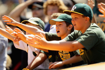 OAKLAND, CA - AUGUST 07:  Fans for the Oakland Athletics try to get a ball during their game against the Texas Rangers at the Oakland-Alameda County Coliseum on August 7, 2010 in Oakland, California.  (Photo by Ezra Shaw/Getty Images)