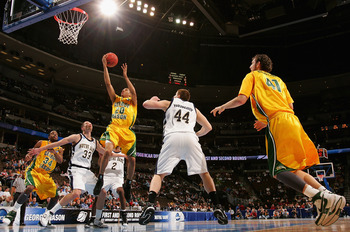 DENVER - MARCH 20:  Cam Long #20 of the George Mason Patriots lays up a shot against Zach Hillesland #33 of the Notre Dame Fighting Irish during the first round of the East Regional as part of the 2008 NCAA Men's Basketball Tournament at Pepsi Center on M
