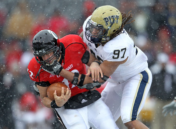 CINCINNATI, OH - DECEMBER 04:  Jabaal Sheard #97 of the Pittsburgh Panthers tackles Zach Collaros #12 of the Cincinnati Bearcats during the Big East Conference game against at Nippert Stadium on December 4, 2010 in Cincinnati, Ohio.  Pittsburgh won 28-10.