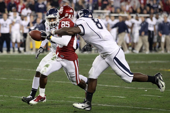 GLENDALE, AZ - JANUARY 01:  Ryan Broyles #85 of the Oklahoma Sooners fumbles the ball as it is stripped by Lawrence Wilson #8 of the Connecticut Huskies alongside Jerome Junior #15 in the second half during the Tostitos Fiesta Bowl at the Universtity of P