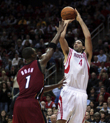HOUSTON - DECEMBER 29:  Luis Scola #4 of the Houston Rockets shoots over Chris Bosh #1 of the Miami Heat during the fourth quarter at Toyota Center on December 29, 2010 in Houston, Texas. Miami won 125-119. NOTE TO USER: User expressly acknowledges and ag