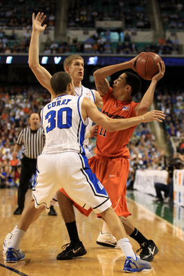 GREENSBORO, NC - MARCH 12:  Erick Green #11 of the Virginia Tech Hokies looks to pass against Seth Curry #30 and Mason Plumlee #5 of the Duke Blue Devils during the second half in the semifinals of the 2011 ACC men's basketball tournament at the Greensbor