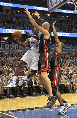 ORLANDO, FL - NOVEMBER 24:  Brandon Bass #30 of the Orlando Magic passes over Zydrunas Ilgauskas #11 of the Miami Heat during a game at Amway Arena on November 24, 2010 in Orlando, Florida. NOTE TO USER: User expressly acknowledges and agrees that, by dow