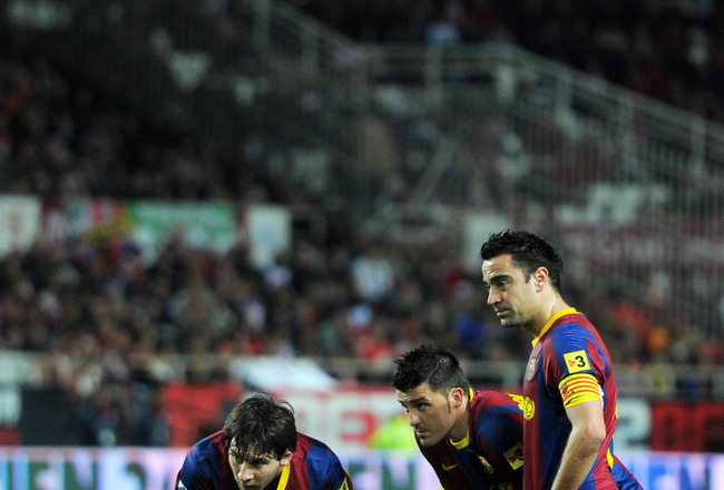 SEVILLE, SPAIN - MARCH 13:  Lionel Messi (L), David Villa (C) and Xavi Hernandez of Barcelona line up a free kick during the la Liga match between Sevilla and Barcelona at Estadio Ramon Sanchez Pizjuan on March 13, 2011 in Seville, Spain.  (Photo by Jaspe