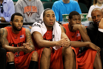 GREENSBORO, NC - MARCH 12:  Malcolm Delaney #23, Victor Davila #14 and Jeff Allen #0 of the Virginia Tech Hokies look on from the bench during the second half against the Duke Blue Devils in the semifinals of the 2011 ACC men's basketball tournament at th