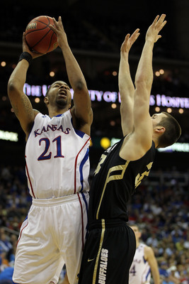 KANSAS CITY, MO - MARCH 11:  Markieff Morris #21 of the Kansas Jayhawks goes up for a shot against Austin Dufault #33 of the Colorado Buffaloes during their semifinal game in the 2011 Phillips 66 Big 12 Men's Basketball Tournament at Sprint Center on Marc