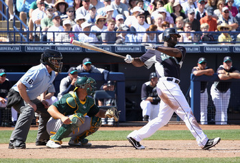 PEORIA, AZ - MARCH 12:  Milton Bradley #15 of the Seattle Mariners hits a RBI double against the Oakland Athletics during the second inning of the spring training game at Peoria Stadium on March 12, 2011 in Peoria, Arizona.  (Photo by Christian Petersen/G