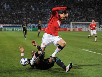 MARSEILLE, FRANCE - FEBRUARY 23:  Dimitar Berbatov of Manchester United is challenged by Stephane Mbia of Marseille during the UEFA Champions League round of 16 first leg match between Marseille and Manchester United at the Stade Velodrome on February 23,