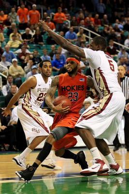 GREENSBORO, NC - MARCH 11:  Malcolm Delaney #23 of the Virginia Tech Hokies goes to shoot against Derwin Kitchen #22 and Bernard James #5 of the Florida State Seminoles during the second half in the quarterfinals of the 2011 ACC men's basketball tournamen