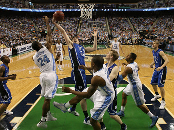 GREENSBORO, NC - MARCH 13:  Ryan Kelly #34 of the Duke Blue Devils fights for the ball against Justin Watts #24 of the North Carolina Tar Heels during the first half in the championship game of the 2011 ACC men's basketball tournament at the Greensboro Co