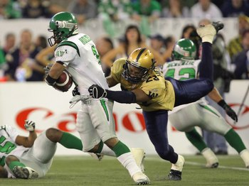 TORONTO - NOVEMBER 25:  O'Neil Wilson #1 of the Saskatchewan Rough Riders breaks away from the tackle of Kyries Hebert #23 of the Winnipeg Blue Bombers during the third quarter in the 95th Grey Cup on November 25, 2007 at the Rogers Centre in Toronto, Ont