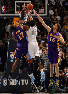 DENVER, CO - JANUARY 21:  Nene #31 of the Denver Nuggets puts up a shot between Andrew Bynum #17 and Pau Gasol #16 of the Los Angeles Lakers at the Pepsi Center on January 21, 2011 in Denver, Colorado. NOTE TO USER: User expressly acknowledges and agrees
