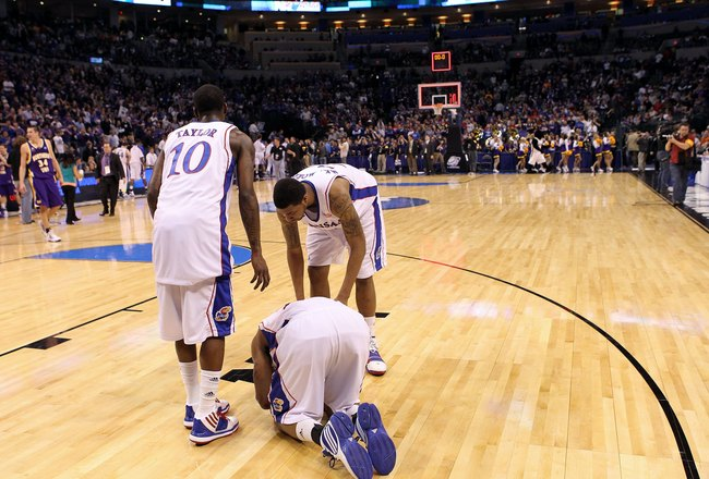 OKLAHOMA CITY - MARCH 20:  (L-R) Tyshawn Taylor #10, Marcus Morris #22 and Markieff Morris #21 of the Kansas Jayhawks remain on the floor dejected after they lost 69-67 against the Northern Iowa Panthers during the second round of the 2010 NCAA men's bask