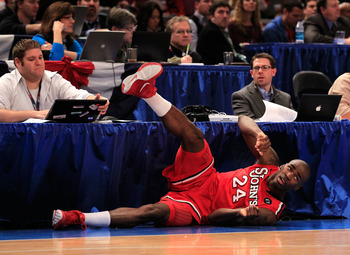 NEW YORK, NY - MARCH 10:  Justin Burrell #24 of the St. John's Red Storm looks up after falling into a press table against the Syracuse Orange during the quarterfinals of the 2011 Big East Men's Basketball Tournament presented by American Eagle Outfitters