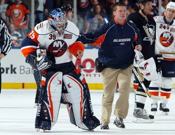 UNIONDALE, NY - NOVEMBER 03: Goaltender Rick DiPietro #39 of the New York Islanders is led off the ice by trainer Garrett Timms after suffering an eye injury against the Pittsburgh Penguins during their game on November 3, 2007 at Nassau Coliseum in Union
