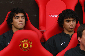 MANCHESTER, UNITED KINGDOM - AUGUST 06:  Rafael Da Silva (L) sits on the bench beside his twin brother and team mate Fabio Da Silva of Manchester United prior to the Pre Season Friendly match between Manchester United and Juventus at Old Trafford on Augus