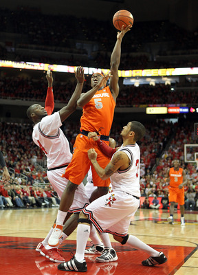 LOUISVILLE, KY - FEBRUARY 12:  C.J. Fair #5 of the Syracuse Orange shoots the ball while defended by Rakeem Buckles #4 and Peyton Siva #3 of the Louisville Cardinals during the Big East Conference game at the KFC Yum! Center on February 12, 2011 in Louisv