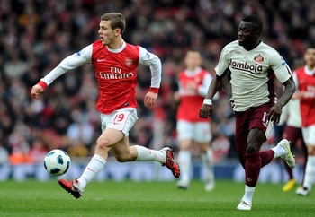 LONDON, ENGLAND - MARCH 05:   Jack Wilshere of Arsenal is pursued by Sulley Muntari of Sunderland during the Barclays Premier League match between Arsenal and Sunderland at Emirates Stadium on March 5, 2011 in London, England.  (Photo by Mike Hewitt/Getty