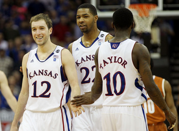 KANSAS CITY, MO - MARCH 12:  Brady Morningstar #12, Marcus Morris #22 and Tyshawn Taylor #10 of the Kansas Jayhawks react after a play against the Texas Longhorns during the 2011 Phillips 66 Big 12 Men's Basketball Tournament championship game at Sprint C