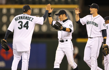SEATTLE - JULY 10:  Starting pitcher Felix Hernandez #34 of the Seattle Mariners celebrates with Ichiro Suzuki #51 and Michael Saunders #55 after defeating the New York Yankees 4-1 at Safeco Field on July 10, 2010 in Seattle, Washington. (Photo by Otto Gr