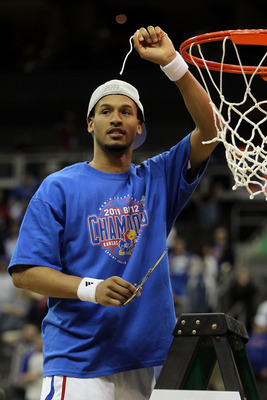 KANSAS CITY, MO - MARCH 12:  Travis Releford #24 of the Kansas Jayhawks celebrates by cutting down the net after defeating the Texas Longhorns 85-73 to win the 2011 Phillips 66 Big 12 Men's Basketball Tournament championship game at Sprint Center on March