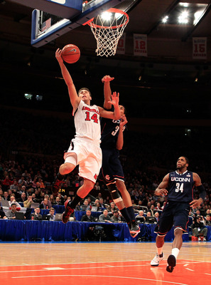 NEW YORK, NY - MARCH 12: Kyle Kuric #14 of the Louisville Cardinals drives to the basket against Jeremy Lamb #3 of the Connecticut Huskies during the championship of the 2011 Big East Men's Basketball Tournament presented by American Eagle Outfitters at M